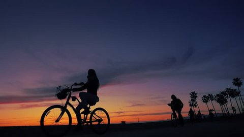 Bicyclists cruising in front of sunset as silhouettes between Santa Monica and Venice Beach in Los Angeles, California. Slow motion.