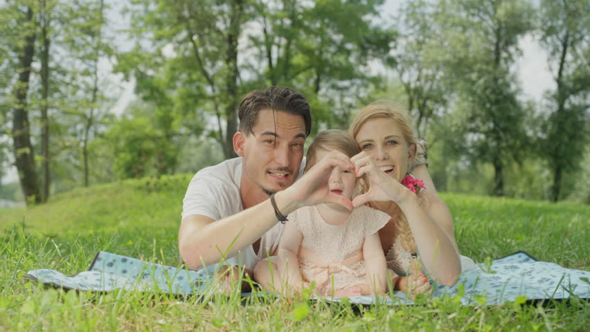 SLOW MOTION, CLOSE UP, DOF: Loving young parents lying on blanket on meadow field in green park, making heart-shaped symbol with their hands. Smiling baby girl in pinky dress enjoying sunny spring day