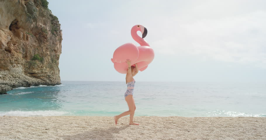 Woman walking on empty beach holding giant inflatable flamingo enjoying summer vacation on tropical beach holiday wearing full one piece swimsuit