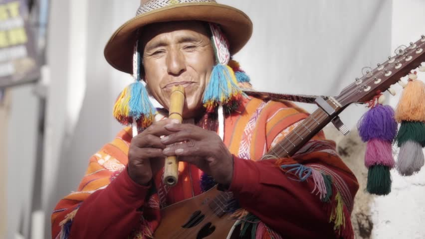 Native quechua man using a colorful handcrafted chullo and a highlander hat, playing flute, typical instrument of Peru on the alleys of Cusco Royalty-Free Stock Footage #24242369