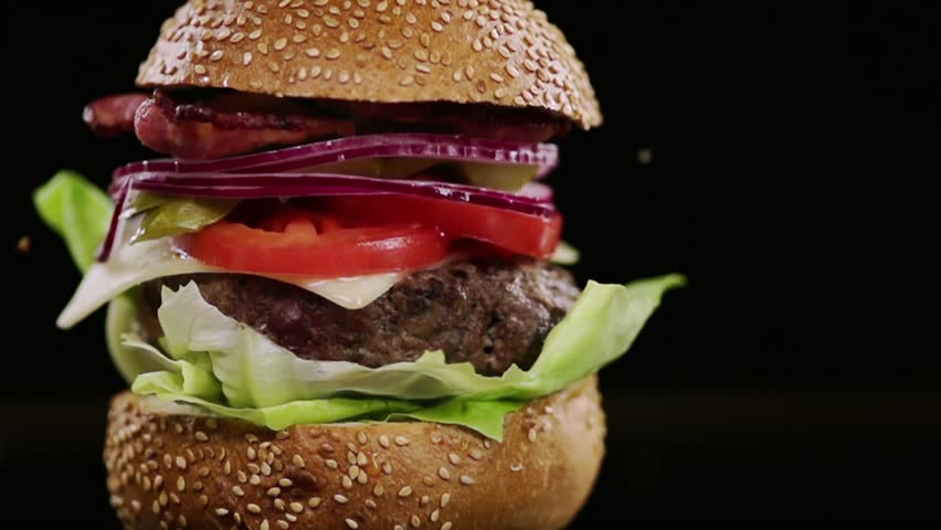 SLOW MOTION FOOD: a piece of bread falls on the finished burger and chips fly
