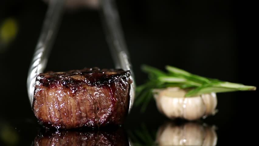 CLOSE UP FOOD: Cooking tongs put filet mignon on a black surface slow motion