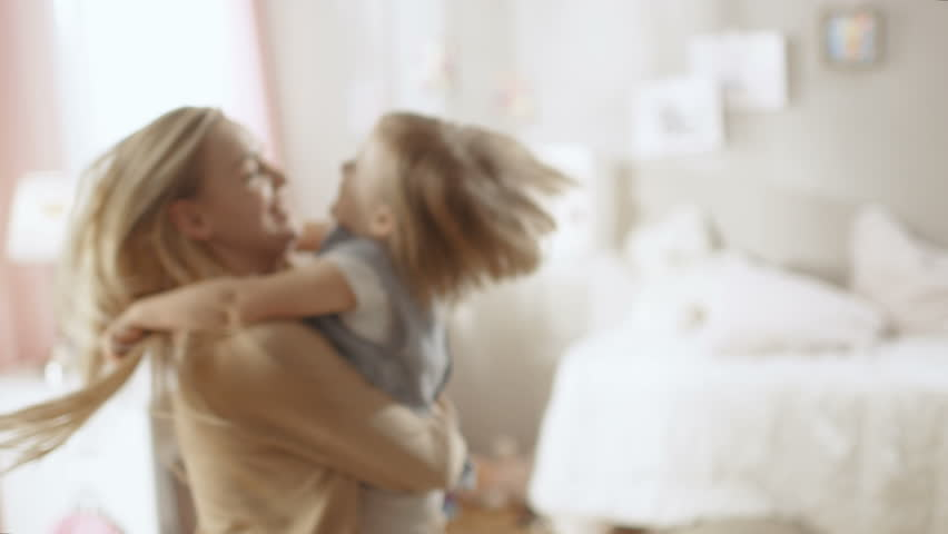 Beautiful Happy Young Mother Holds Her Cute Little Daughter in Her Hands and Spins With. Both are Laughing. Shot on RED EPIC-W 8K Helium Cinema Camera.