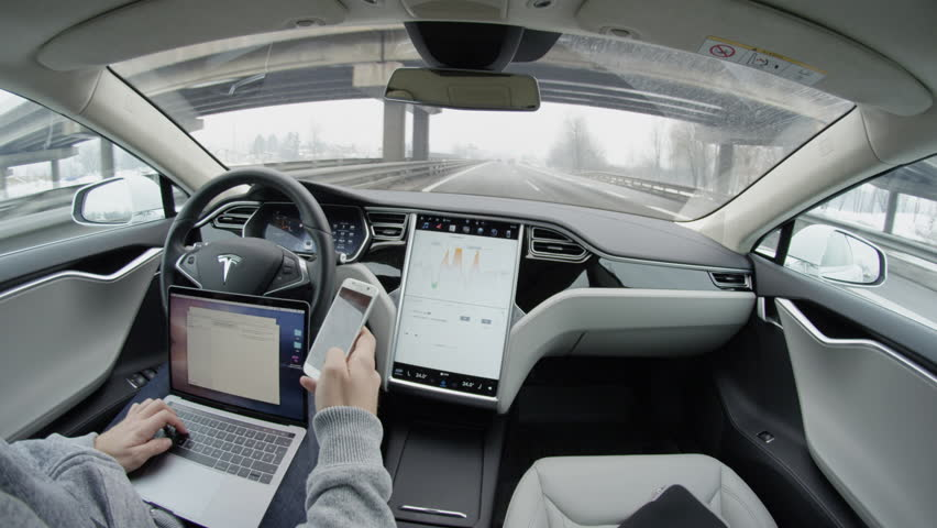 AUTONOMOUS TESLA CAR, FEBRUARY 2016: Business correspondence via smartphone and laptop from the car while traveling in self-driving autonomous automated driverless Tesla Model S electric vehicle
