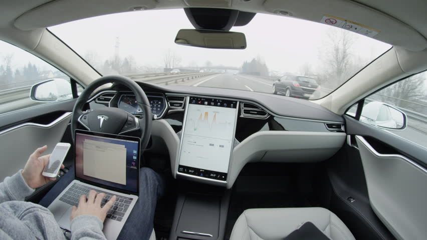 AUTONOMOUS TESLA CAR, FEBRUARY 2016:  Self-driving Tesla Model S car autopilot demanding driver attention to hold steering wheel & take control on highway. Man working on laptop & texting on mobile