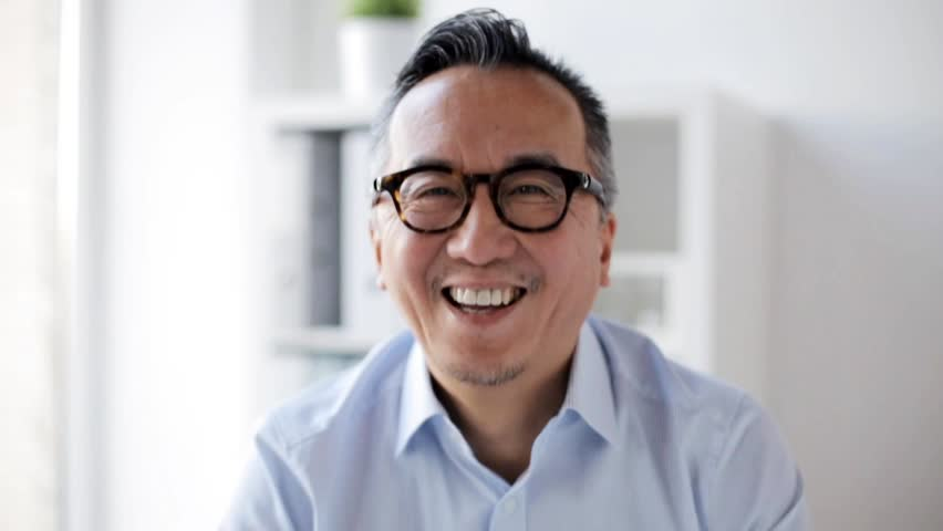 Business, people, emotion and facial expression concept - happy smiling asian businessman at office