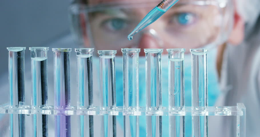 In a laboratory, a scientist with a pipette analyzes a colored liquid to extract the DNA and molecules in the test tubes. Concept: research, biochemistry, nature, pharmaceutical medicine #24263996