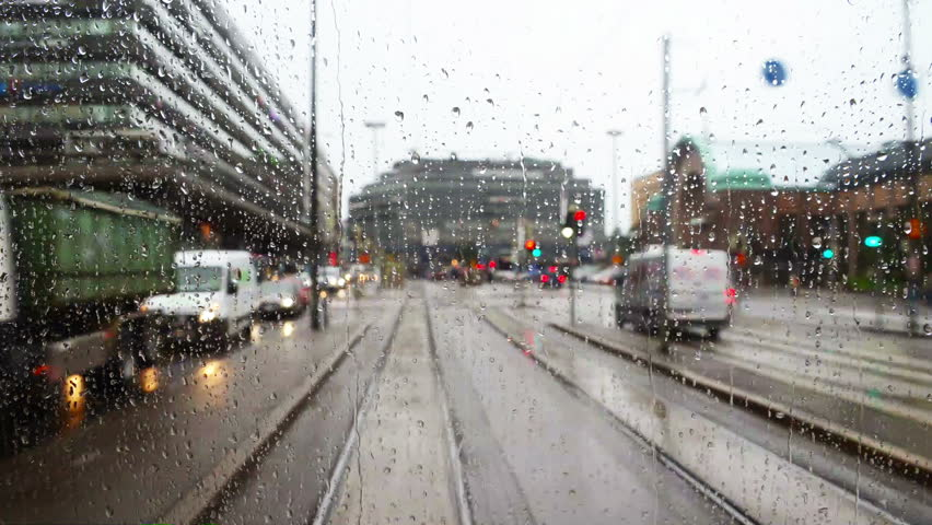 Helsinki, Finland. Riding tram in the city center of Helsinki the capital of Finland. Car and tram traffic. Cloudy rainy day, many shops, cafes. Rain drops on the window, time-lapse