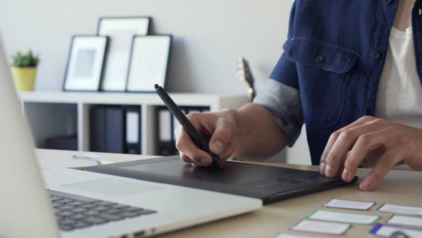 Closeup of freelance graphic designer sketching on tablet, working from home office. | Shutterstock HD Video #24287576