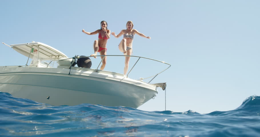 Women jumping off boat into ocean two girls jump into clear blue water from sailboat enjoying active lifestyle summer holiday travel vacation adventure | Shutterstock HD Video #24291641