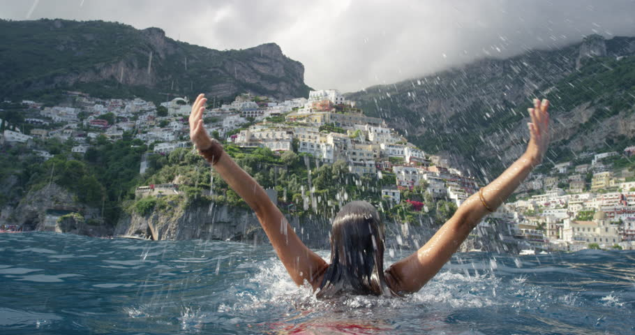 Young tourist woman jumping out of water with arms up looking at Positano town in background Swimmer girl Celebrating Italian Vacation enjoying European summer holiday travel adventure in Amalfi Italy #24291659