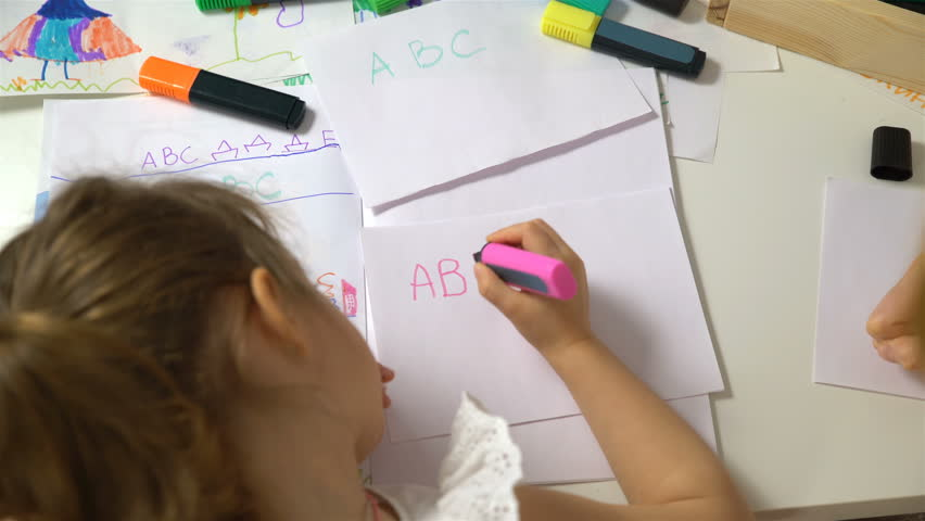Distance learning at home. Mother and daughter are learning to write. Adult woman teaches child the alphabet. Dolly shot.