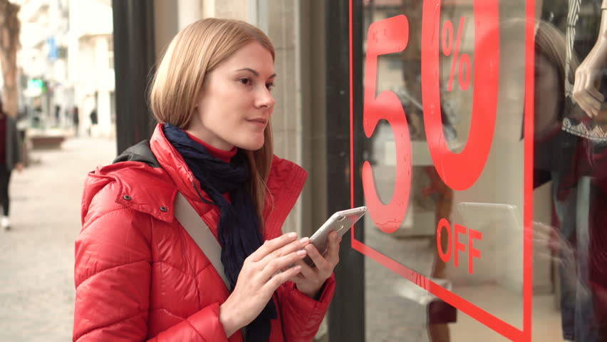 Beautiful attractive young woman near window shop. Sales signs. Reading QR-codes by smartphone. | Shutterstock HD Video #24324212