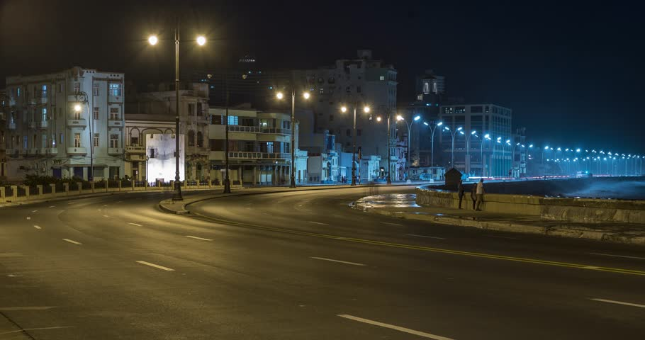 Night time-lapse of a road along the El Malecon waterfront in Havana Cuba, with old apartment buildings in the background.