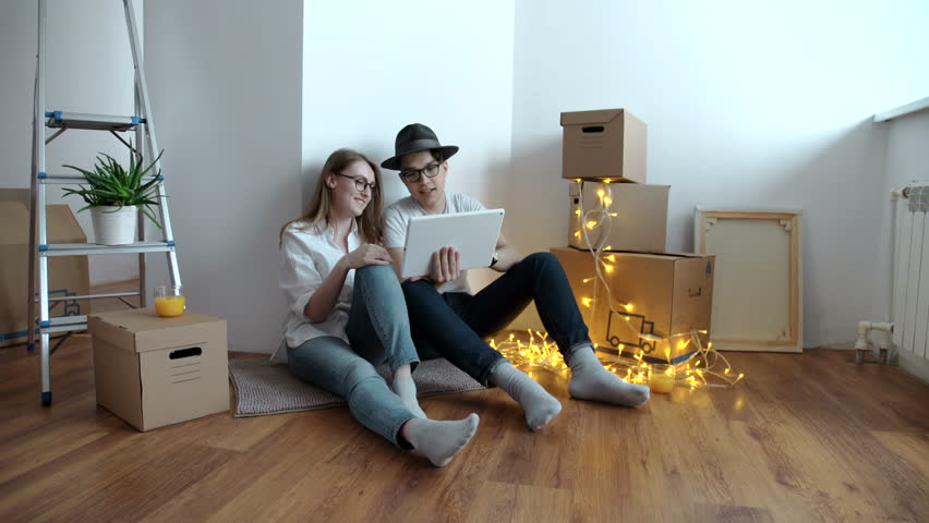 Young couple moving in new home.Sitting on floor and relaxing after cleaning and unpacking.Using tablet. #24327872