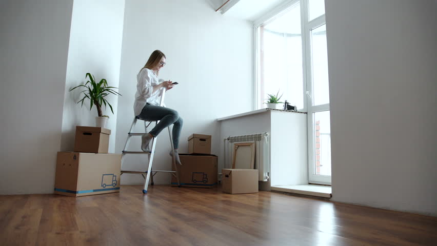 Attractive young woman is moving, standing among cardboard boxes, using a smartphone and smiling | Shutterstock HD Video #24327950