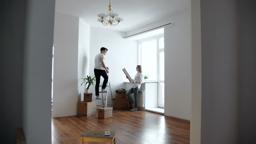 Young couple choosing point for picture on wall at home | Shutterstock HD Video #24327974