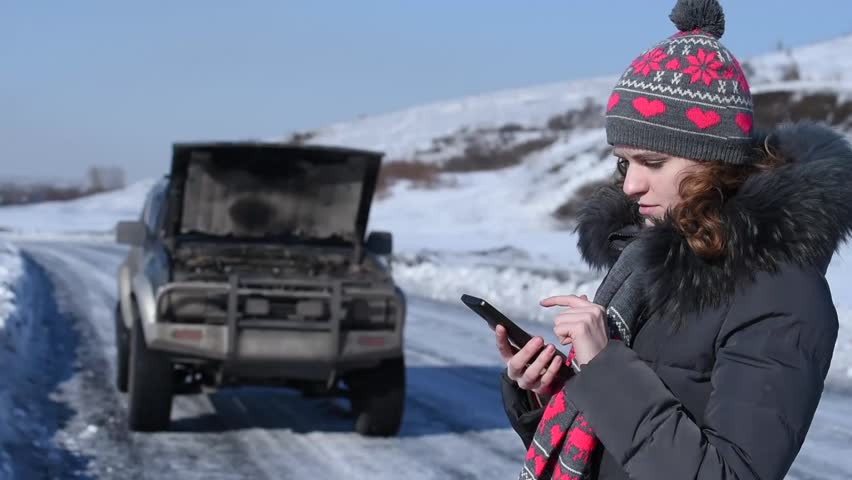 Broken car on a winter road and a woman calling on the phone crying and asking for help | Shutterstock HD Video #24339656