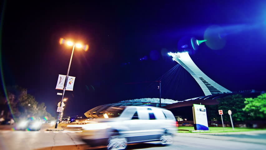 MONTREAL - OLYMPIC STADIUM - JUNE-2012: Night time lapse of Traffic and cars traveling on Pierre-de-Coubertin Avenue 14th of June 2012 - Montreal Olympic Stadium