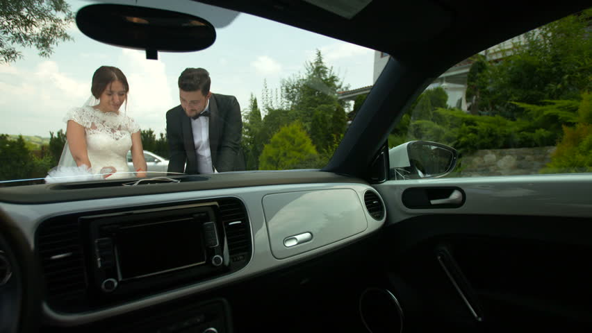Bride and groom outdoor romantic scene. Looking at a map, next to a car. Setting the next travel destination. | Shutterstock HD Video #24350990