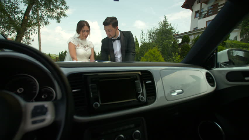 Bride and groom outdoor romantic scene. Looking at a map, next to a car. Setting the next travel destination. | Shutterstock HD Video #24351209
