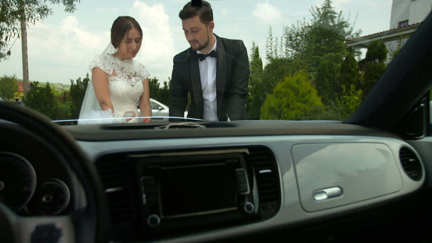 Bride and groom outdoor romantic scene. Looking at a map, next to a car. Setting the next travel destination. | Shutterstock HD Video #24351245