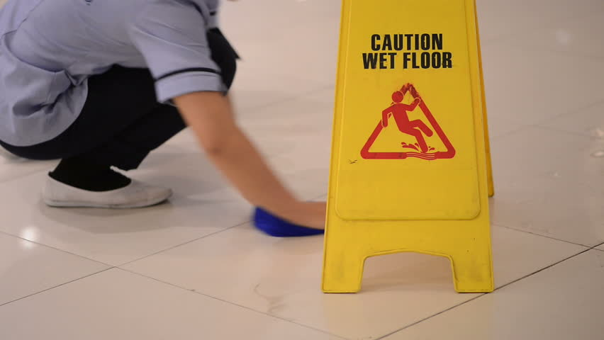 Sign showing warning of caution wet floor and Worker with cloth cleaning hall floor of public business building. | Shutterstock HD Video #24360149