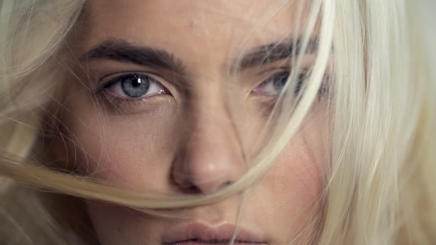 Close-up face of a beautiful blonde with blue eyes in Slow Motion