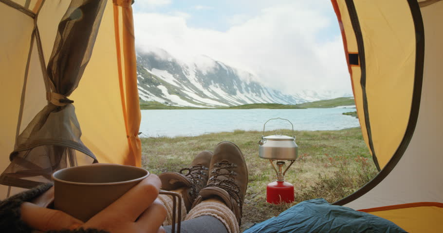 Camping woman lying in tent Close up of Girl feet wearing hiking boots drinking warm drink relaxing on vacation POV #24370100