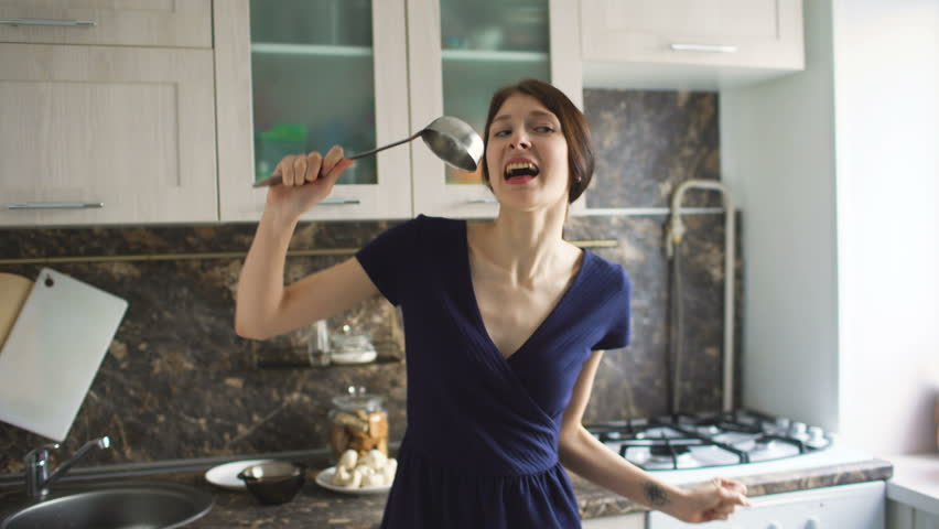 Funny woman housewife cook dance and sing with big ladle while cooking in modern kitchen at home #24370217