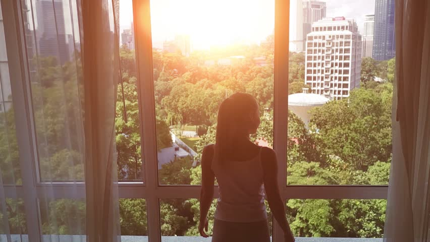 Slow motion. Young woman uncover the big window and looking out her apartment on the city buildings. Sunrise in the city.