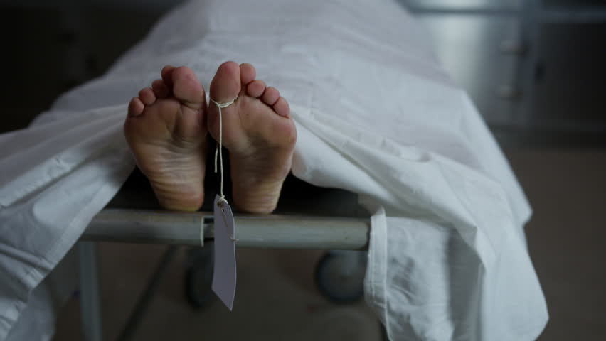 Morgue - female feet on gurney with toe tag dead body