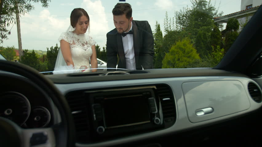 Bride and groom outdoor romantic scene. Looking at a map, next to a car. Setting the next travel destination. | Shutterstock HD Video #24383309