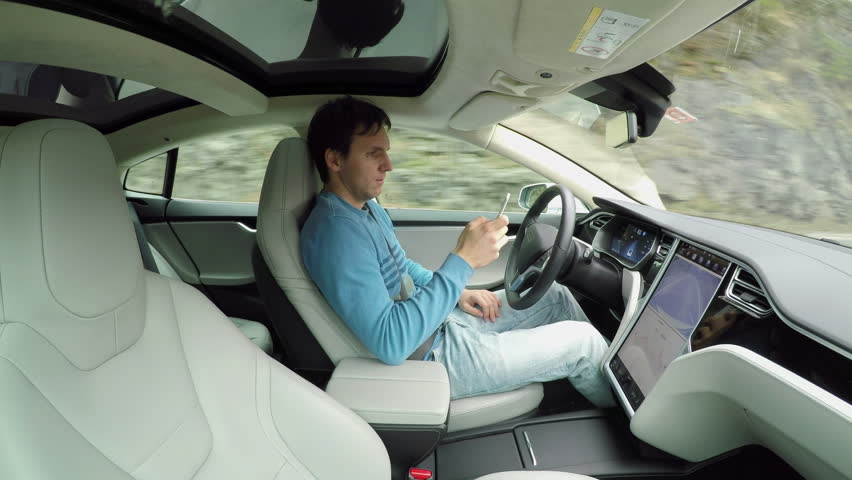 Male driver writing messages on smartphone sitting behind self-driving steering wheel in autonomous autopilot driverless electric car traveling along the countryside road. Man texting in the vehicle