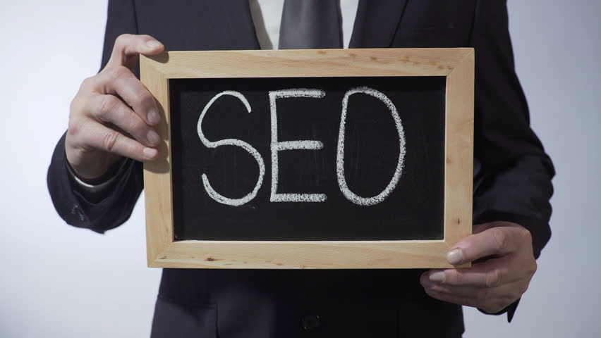 SEO written on blackboard, businessman holding sign, business concept, strategy | Shutterstock HD Video #24398447