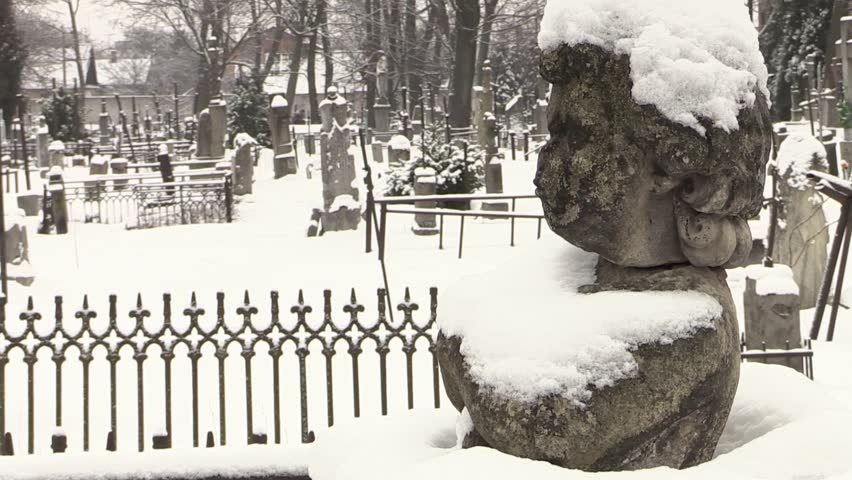 Sculpture of a Little Angel in the cemetery in winter