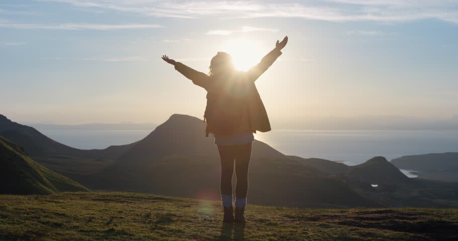 Woman with arms raised on top of mountain looking at Sunset view Hiker Girl lifting arm up celebrating life scenic nature landscape enjoying vacation travel adventure Isle of Skye Scotland Royalty-Free Stock Footage #24428360