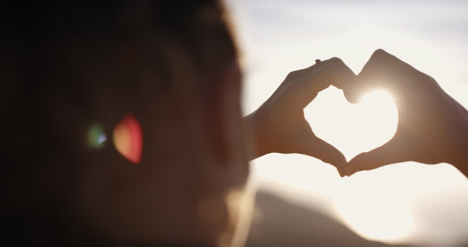 Beautiful Woman making heart shape with hands at sunset Girl holding up love symbol gesture with orange sun flare  | Shutterstock HD Video #24428369