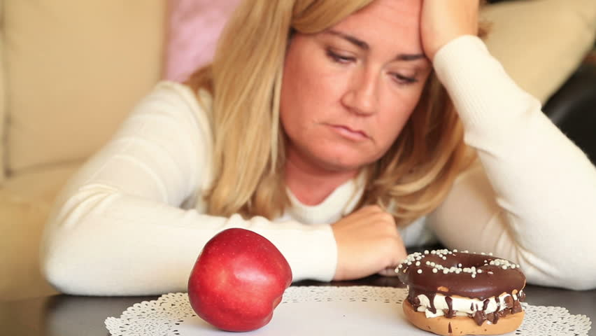 Attractive middle aged woman deciding between a healthy and unhealthy. Diet and choice people concept   Shutterstock HD Video #24431861