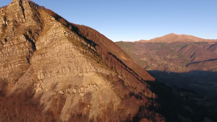 Aerial shot, autumn landscape in the high mountains in Italy with coniferous wood, sun high in the sky, filmed with drone, 4K | Shutterstock HD Video #24437435