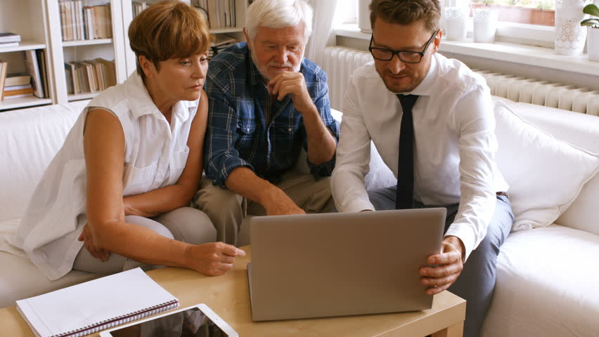 Senior Caucasian couple planning their investments with financial advisor on laptop at home