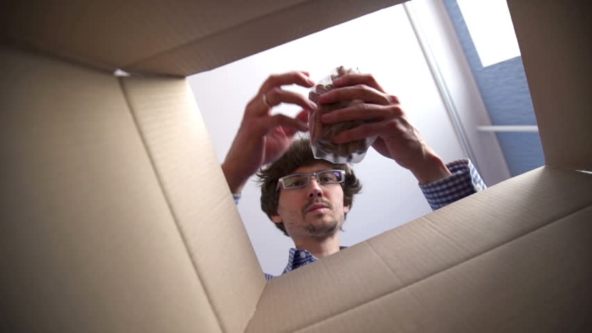Man opening a Food delivery box at home. Food delivery services during coronavirus pandemic for working from home and social distancing. Shopping online.