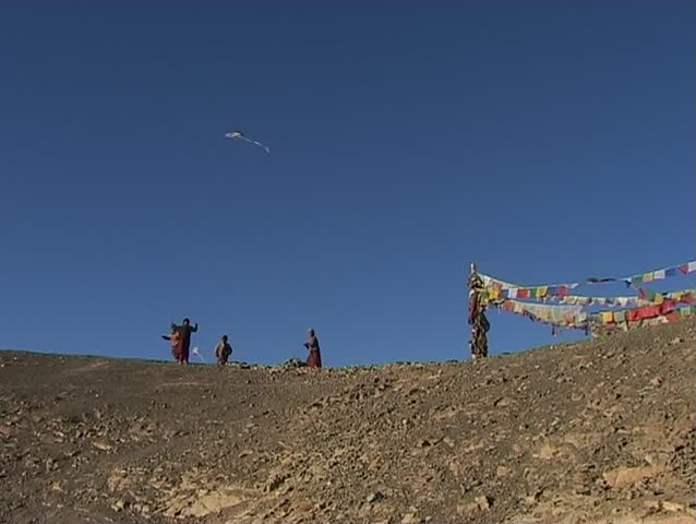 Young Buddhist monks flying a kite in the Himalayas