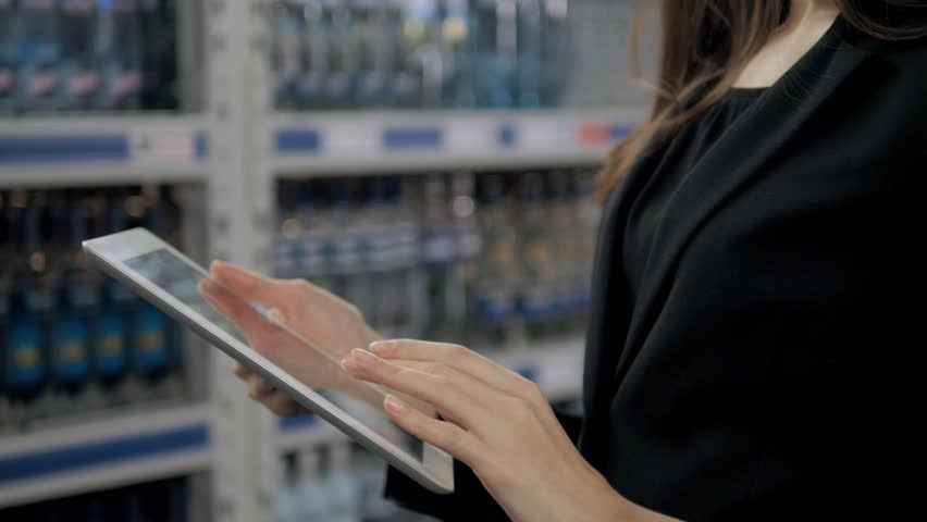 Sale, shopping, consumerism and people concept - close up of young woman with tablet pc computer in market, supevisor in alcohol store | Shutterstock HD Video #24490058