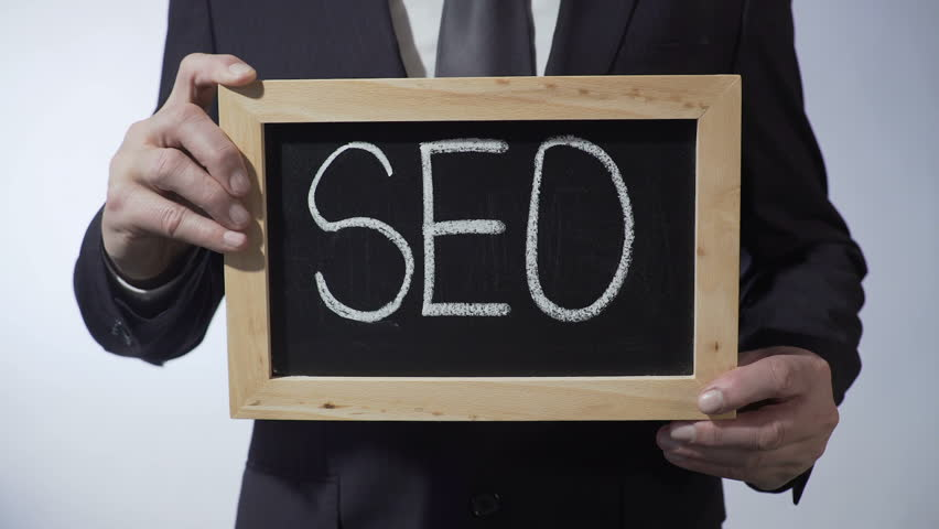 SEO written on blackboard, businessman holding sign, business concept, strategy | Shutterstock HD Video #24503594