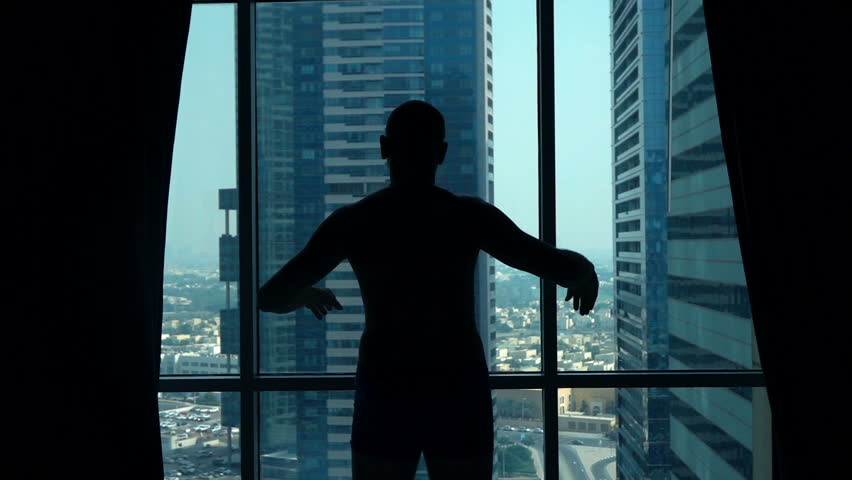 Silhouette of young man admiring view from window at home, super slow motion 240fps  #24503600