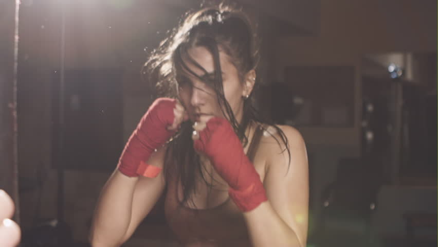 The energetic woman in the gym boxing pear
