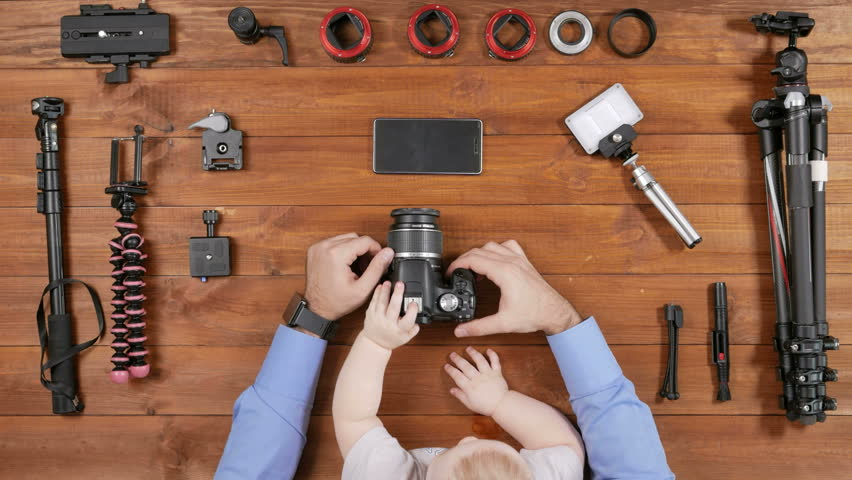 Photographer father with a young son checked the camera before shooting. Wooden table top view. Toddler touching a button. Equipment for shooting on the table. | Shutterstock HD Video #24522380