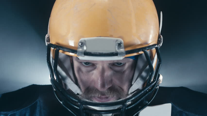 EXTREME CU Portrait of Caucasian male American football player looking into camera against black background. RAW edited footage