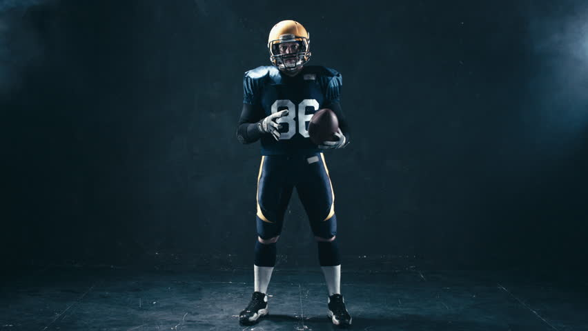 Full portrait of Caucasian male American football player holding a ball and pointing into camera. 4K UHD RAW edited footage